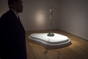 """A guard stands watch over Alberto Giacometti's """"L'homme Au Doigt"""" (Pointing man) sculpture at Christie's Auction House in the Manhattan borough of New York"""