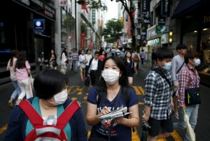 Chinese tourist wearing masks to prevent contracting Middle East Respiratory Syndrome (MERS) walk at Myeongdong shopping district in central Seoul