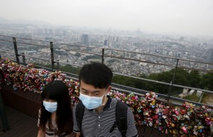 """A couple wearing masks to prevent contracting MERS, tours as central Seoul is seen in the background at """"N Seoul Tower"""" located atop Mt. Namsan in Seoul"""