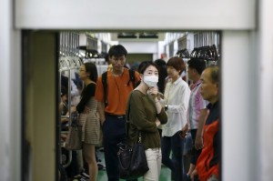 A passenger wearing a mask to prevent contracting Middle East Respiratory Syndrome (MERS) stands inside a train in Seoul