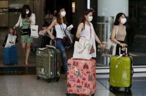 South Korean visitors arriving from Seoul are seen wearing masks at Hong Kong Airport in Hong Kong