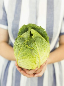 Studio shot of woman holding fresh cabbage